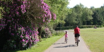Man and girl cycling in Drumpellier Park